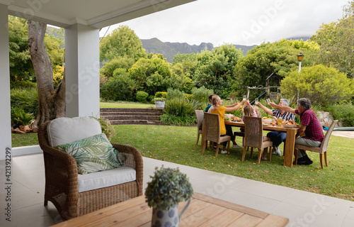 Caucasian three generation family sitting at table making a toast during meal in garden