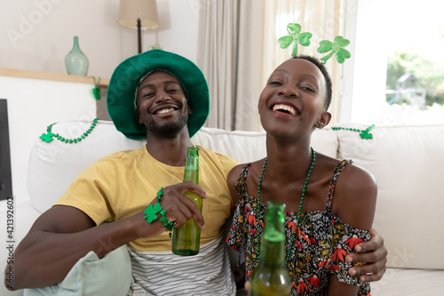 African american couple wearing st patrick's day costumes laughing and holding glasses of beer