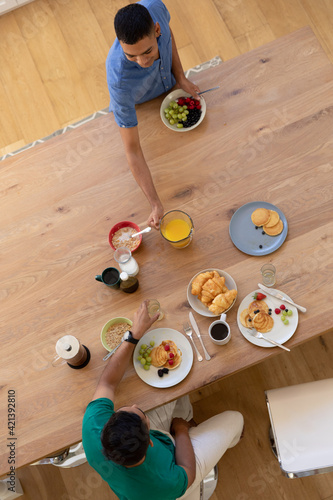 Diverse gay male couple eating breakfast together and talking