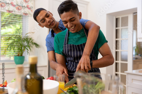 Diverse gay male couple spending time in kitchen cooking together and smiling