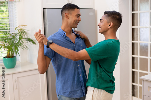 Diverse gay male couple spending time in kitchen dancing