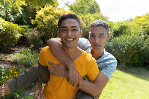 Portrait of diverse gay male couple spending time in garden embracing and smiling