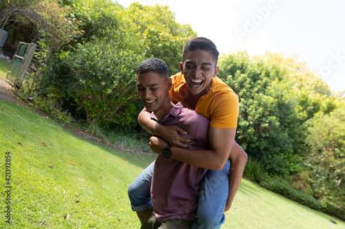 Diverse gay male couple spending time in garden embracing and smiling