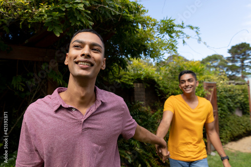 Diverse gay male couple holding hands and walking in garden