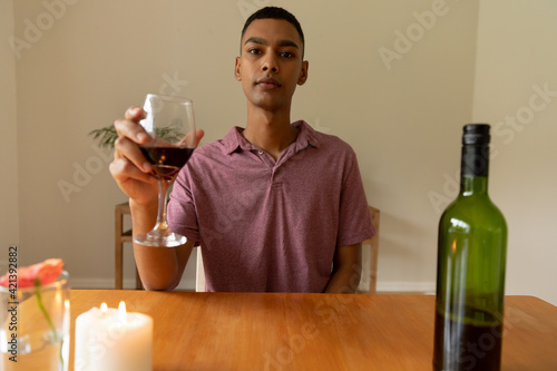 Portrait of mixed race man holding glass of red wine looking at camera