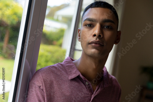 Portrait of mixed race man leaning on window looking at camera