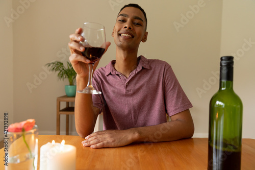 Portrait of mixed race man holding glass of red wine looking at camera smiling