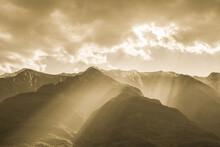 Sunrays Break Through Dense Clouds And Lighten Up Snowy Mountains And Dark Valleys
