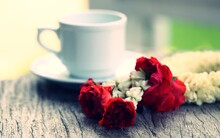 Close-up Of Red Roses  And White Hot Drink Cup On Table Blur Background
