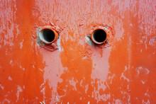 Full-frame Shot Of Weathered Orange Wet Wall And 2 Eye-shaped Holes