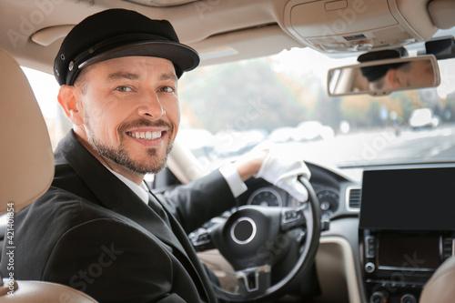 Fotografia Handsome chauffeur driving luxury car