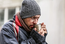 Poor Homeless Man With Cup Of Hot Drink Outdoors On Winter Day