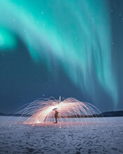 Magnificent Display Of Northern Lights, Aurora Borealis With Person Spinning Sparks, Fireworks, Steel Wool Below The Stunning, Dancing Sky.