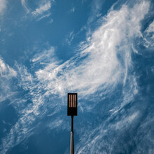 Centred Lightpost With Swirly Clouds For A Background