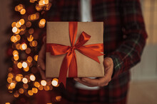 Midsection Of Man Holding Christmas Present At Home