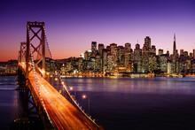 Illuminated Bridge Over River In City At Night