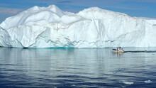 A Boat In Front Of An Iceberg On The Coast Of Greenland In The Davis Strait