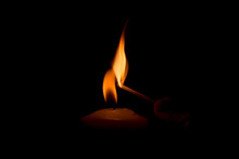 Cropped Image Of Person Igniting Candle In Darkroom