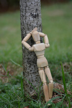 A Wooden Mannequin Leaning On The Tree Trunk
