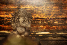 Statue Of Ganesha On Ancient Brick Wall Background.