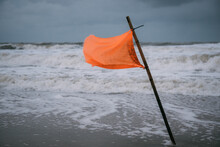 Red Flag On Sea Against Sky