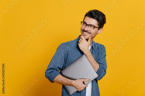 Attractive confident smart guy in glasses and in a denim shirt, holding a laptop at hand, looks thoughtfully towards empty space aside touching his chin, smiling, isolated orange background,copy space