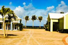 Houses And Palm Trees On Beach Against Sky