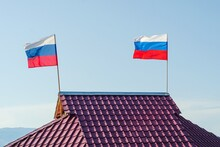 Two Russian Flags Are Developing On The Roof Of The House Against The Sky.