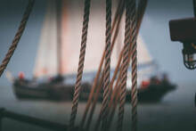 Close-up Of Rope With Blurry Sailing Ship In Background