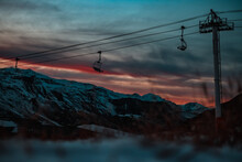 Low Angle View Of Snowcapped Mountain And Ski Lift Against Dramatic Sky During Sunset