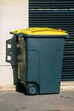 Garbage Bin On Sidewalk Against Wall In City