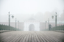 Foggy Atmospheric Landscape Of Wooden Boardwalk Bridge With Retro Elegant Lanterns On The Sides And Silhouette Of Man From The Back Walking With Bicycle To The Entrance Of White Arch In Old Building