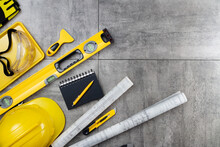 Contractor Theme. Tool Kit Of The Contractor: Yellow Hardhat, Libella, Hand Saw. Plans And Notebook On The Gray Tiles Background.