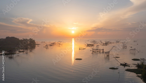 Local fishing trap net in canel, lake or river at sunset. Nature landscape fisheries and fishing tools lifestyle at Pak Pha, Phattalung, Thailand. Aquaculture farming.
