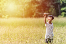 Cute Asian Child Playing Airplane In The Park Outdoors Happy Asian Boy Holding A Plane Runs In A Meadow With Sunset.