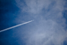 Low Angle View Of Airplane Flying Against Blue Sky
