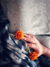 Close-up Of Hand Holding Orange And Yellow Flower Against Gray Bedding And Silk Scarf.