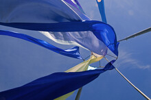 Low Angle View Of Fabric Waving Against Blue Sky
