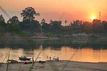 Fishermen On Mekong River In Cambodia During Sunset