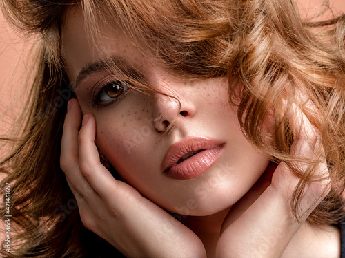 Beautiful face of an white woman. Beautiful brown haired with stylish short hairstyle. Woman with a curly hair. Sensual young woman with freckles on face. Attractive girl with a brown makeup.