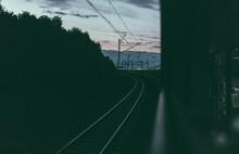 Railway Tracks By Electricity Pylon Against Sky