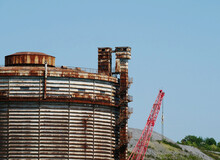 Rusty Gasometer In Demolished With Red Self-propelled Crane.