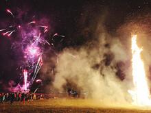 Group Of People Enjoying Firework Display At Night