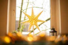 Close-up Of Yellow Decoration Hanging Against Window