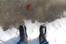 Feet In Boots In A Frozen Puddle