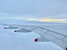 Landscape View Of Airplane Wing Surrounded By Clouds And Sunset In The Distance