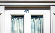House Number 41 On A White Wooden Front Door In London With Curtains