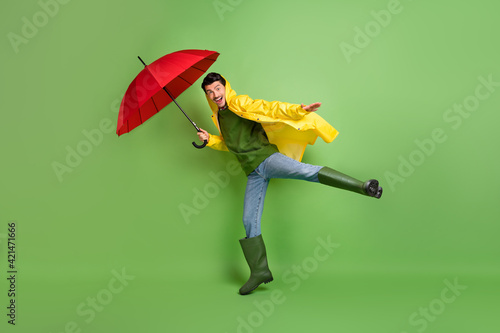 Valokuva Full size profile photo of brunet optimistic guy fly with umbrella wear cloak bo