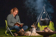 Young Woman And Her Australian Shepherd Outside By A Campfire. Reading A Book At Dusk. Bread, Cheese And Wine On The Table. Large Saucepan Hangs Steaming Over The Fire In Winter