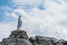 White Statue Of Virgin Mary, Mother Of God, Placed On Top Of The Mountain.